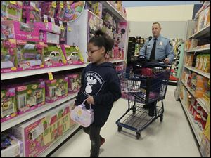 Lauran Coats, 9, shopping with TPD officer Adam Eilerts. Both Lauren and her brother Michael, 8 [not pictured], bought gifts for other members of their family.