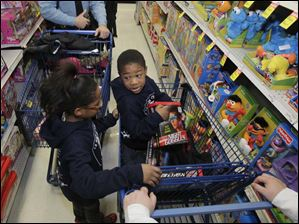 Lauren Coats, 9, left, and her brother Michael Coats, 8, talk about the gifts they have put in their carts for others in their family.