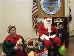 Savannah Cole, 3, right, with an elf, left, and Santa Claus at the Toledo Police Patrolman's Association's hall.