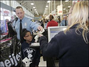 TPD officer Adam Eilerts gives cash for a present for Lauren Coats, 9, to Meijer's employee Julie Sengstock, of Toledo.