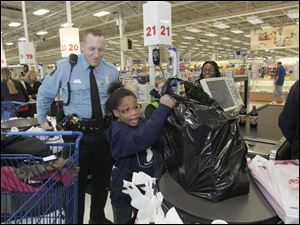 TPD officer Adam Eilerts helped Lauren Coats, 9, as she bought gifts for her family as well as for herself.