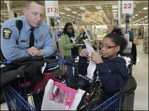 TPD officer Adam Eilerts suggests to Lauren Coats, 9, that she keep the receipt. They had shopped together for Coats and her family.