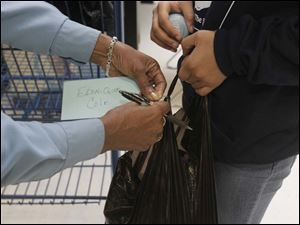 TPD officer Valerie Lewis ties an evidence tag onto Ebonique Cole's bag when they were done shopping. Cole had purchased pants, clothes, underclothes and other items with the money.