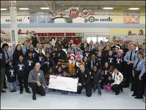 The symbolic check from Meijer, the store's manager, children, the police and Child Service Bureau employees gather for a photo before shopping.