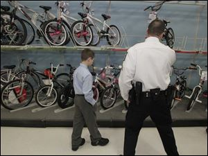Nicholas Comment, 11, left, and TPD Sgt. Daniel Raab look over bicycles. Comment had dressed up so he would look nice for the officers.