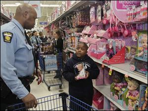 Cato Hornbeak, Right, explains to TPD officer Leon Cavanaugh that he needs to get a toy for his three-year-old sister.