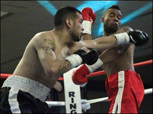 Rafael Gramajo, left, and Micah Branch, right, trade punches during their fight at the Purgatory Fight Series All Pro Boxing event.