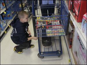 Kross Kerschner, 6, puts a skateboard on the cart. He is with TPD officer Gabe Greenwalt.