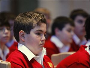 Michael Boutros, 12, a seventh grade student at Franciscan Academy, prays during a memorial service for the Sandy Hook School shooting victims in Newtown Connecticut, at Our Lady Queen of Peace Chapel in Sylvania.