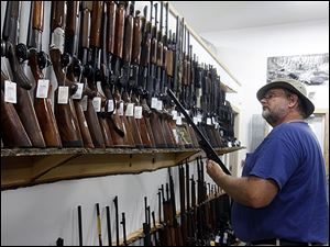 Ryan Brown shops at Cleland's Outdoor World in Swanton earlier this year. The string of deadly shootings during the year has made some gun owners rethink their position on added restrictions.