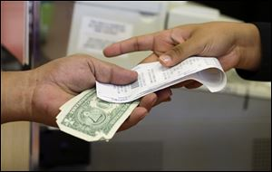 A cashier hands a customer his change and receipt during a transaction at a Sears store, in Henderson, Nev.