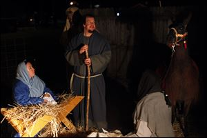 Kelly and Kyle Tarry portray Mary and Joseph in a live version of the Nativity during the fifth annual Christmas tree lighting ceremony at Strawberry Acre Park in Holland, Ohio. Area ministers, like their parishioners, spend time on Christmas with family members.