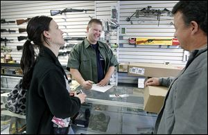 Todd Bruning, center, owner of Todd's Guns in Lambertville, speaks with Melissa Green and her father-in-law, Mark Busby, as he sells Ms. Green, who is soon to receive a teaching degree, a gun. She says educators should be able to carry a gun to protect their students.