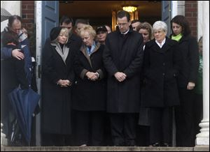 Connecticut Gov. Dan Malloy, center, stands with other officials to observe a moment of silence while bells ring 26 times in Newtown, Conn. today.
