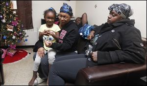 Miyetta Neal, 5, sits on the lap of her mother, Bernice Neal, as Deandre Hooks and Quentorria Snowden talk about the loss of their 1-year-old daughter, Keondra Hooks.