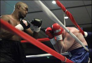 Tim Washington of Toledo pummels Alen Basic during their fight at the Grand Plaza Hotel on Friday night.