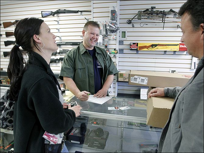 Todd Bruning, owner of Todd's Guns in Lambertville, Mich Todd Bruning, center, owner of Todd's Guns in Lambertville, speaks with Melissa Green and her father-in-law, Mark Busby, as he sells Ms. Green, who is soon to receive a teaching degree, a gun. She says educators should be able to carry a gun to protect their students.