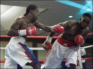 Adrian Wilson, left, hits George Martin with a left during their fight at the Purgatory Fight Series All Pro Boxing event.