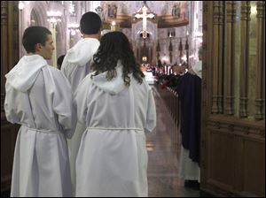 From left: Central Catholic students Tony Mossing, Aaron Powers and Megan Hoffman prepare to participate in Mass at Rosary Cathedral in Toledo, Ohio.