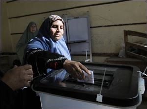 An Egyptian woman casts her vote for the second round of a referendum on a disputed constitution drafted by Islamist supporters of President Mohammed Morsi in Giza, Egypt, Saturday, Dec. 22, 2012. (AP Photo/Amr Nabil)