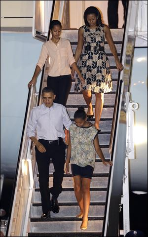President Barack Obama arrives today with first lady Michelle Obama, top, and daughters Malia, top left, and Sasha, bottom right, at Honolulu Joint Base Pearl Harbor-Hickam in Honolulu, for the start of their holiday vacation.