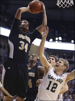 Wofford center Lee Skinner scores over Xavier guard Brad Redford (12) in the second half Saturday in Cincinnati.