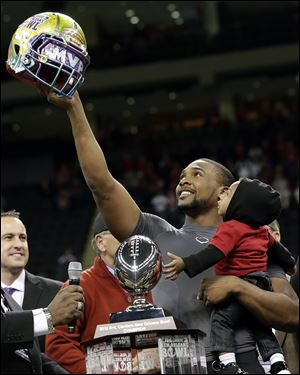 Louisiana-Lafayette quarterback Terrance Broadway holds his son Terrance and the New Orleans Bowl helmet after defeating East Carolina in the New Orleans Bowl