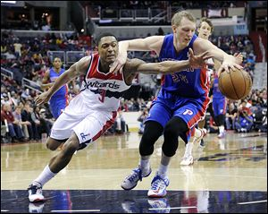 The Wizards' Bradley Beal (3) reaches for the ball, but is held back by the Pistons' Kyle Singler during the second half on Saturday.
