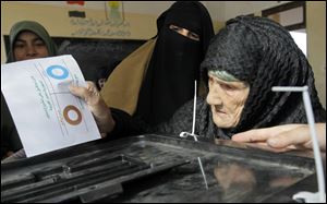 Amnah Sayyed Moussa, 85, casts her vote for the second round of a referendum on a disputed constitution drafted by Islamist supporters of President Mohammed Morsi in Giza, Egypt.