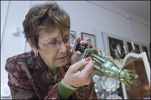 Connie Hoffman inspects markings on the bottom of a small piece at her shop, Adams Street Antiques.