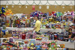 A volunteer is surrounded by tables full of donated toys that await sorting at the town hall. At Newtown United Methodist Church, hundreds of prayer shawls fill a storage closet, and the donations keep coming.