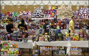 Volunteers look over tables full of donated toys at the town hall in Newtown, Conn.