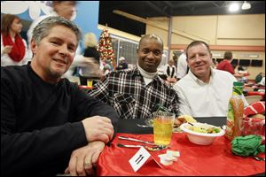 Bernard Clark, center, a Cherry Street Mission resident, joins Greg Scerba, left, and Frank Borgelt, both of CedarCreek Church, at the holiday meal in Perrysburg Township.
