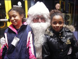 Savannah Robinson, left, and Selena Herrera, both 8, meet Santa during the Boys and Girls Clubs Christmas Party.