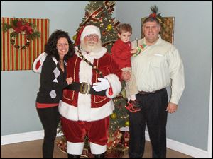 The Swade family Sarah, Nicholas, and William pose for a photo with Santa at Highland Meadows Golf Club's Brunch with Santa.