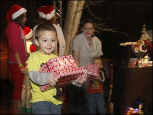Adam Chandler, 3, son of Andrea Chandler, carries his present from Santa during the Big Brothers, Big Sisters Christmas party at Cedar Creek Church.