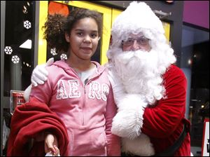 MacKayla Bebley, 12, meets Santa at the Boys and Girls Clubs Christmas Party at the Imagination Station.