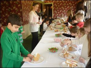 Children create houses at the Sylvania Country Club's Gingerbread House Building Workshop.