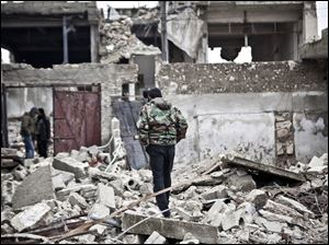 Free Syrian Army fighters walk amid the ruins of a village situated a short distance from an area where fighting between rebels and government forces continues, Saturday.