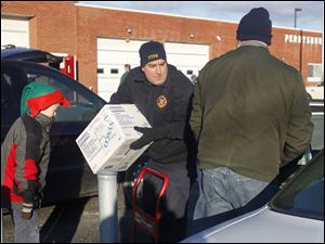 Levi Brice, 8, left, stands ready to help as Matt Homik, center, and  Tom Brice load a car with food on December 22, 2012.