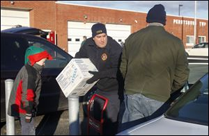Levi Brice, 8, left, stands ready to help as Matt Homik, center, and  Tom Brice load a car with food. The recipient was among about 100 served Saturday.