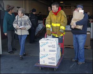 Rossford Fire Explorer Justin Klocko, center, and volunteer firefighter Sara Rynski, right, help distribute food. The annual Operation Bread Basket was Saturday in Perrysburg Township.