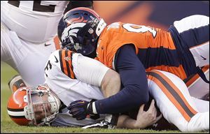 Cleveland Browns quarterback Brandon Weeden, left, is sacked by Broncos defensive end Elvis Dumervil in the third quarter Sunday in Denver. Weeden left the game after that play with a right shoulder injury and did not return. The Browns lost 34-12.