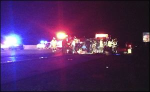 Officials work the scene of a head-on collision involving two minivans on Interstate 75 on Sunday near Franklin, Ohio. The collision killed four people, including a 7-year-old boy, from two different families in Ohio and Tennessee just two days before Christmas. Two other children were critically injured in the collision.