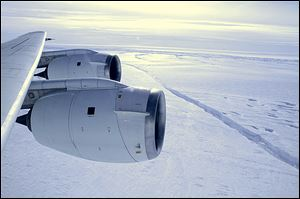 A NASA DC-8 research plane flies over the crack form-ing across the Pine Island Glacier ice shelf in Antarctica.