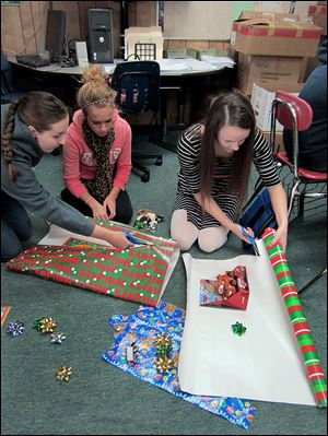 Abigail Spencer, left, Bailey Sharp, and Katie Hill, Spanish students at Bedford High School in Temperance, wrap presents to be given to one of three Toledo-area needy families.