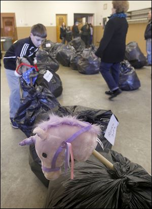 Volunteer Scott Upton, 12, helps with the bags of toys during the collection drive.