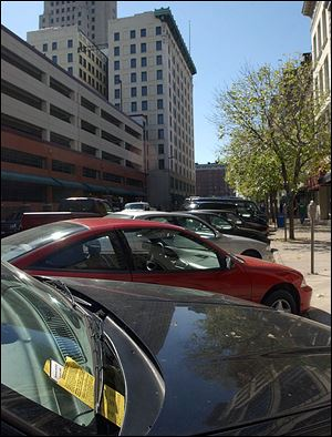 A parking ticket is visible on the windshield of a car parked at a meter on Superior Street in downtown Toledo.