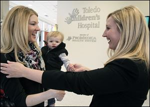 Kari Stausbaugh holds her son Pierce as they are greeted by Christi Rotterdam, executive director of Toledo Children's Hospital Foundation.