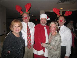 Toledo Ski Club Christmas Party co-chairman Karen Wolfe, 'reindeer' Peter Mainhardt, 'Santa' Jim Wallace, co-chariman Ginger Safford, and 'reindeer' Ed Brown revel in the holiday spirit.